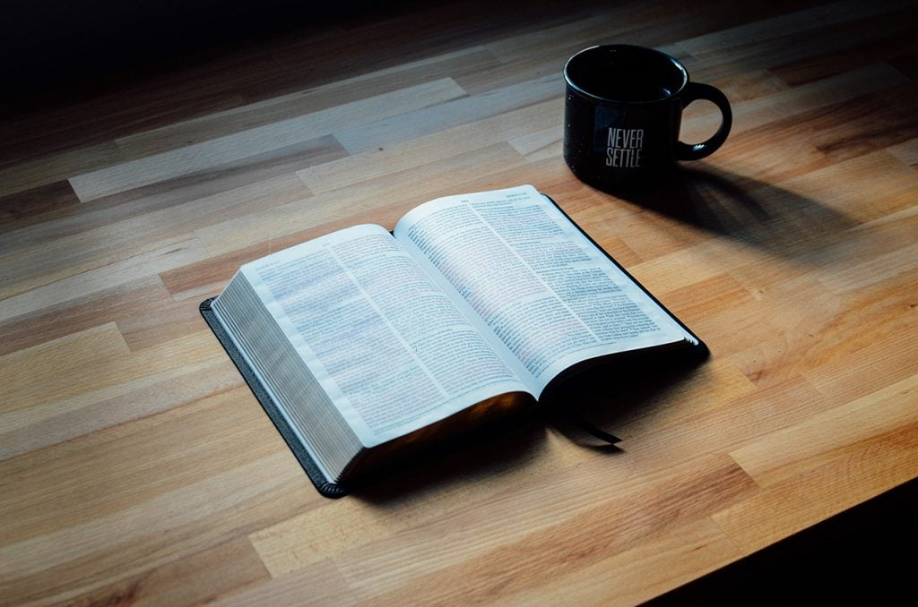 Open Bible and Coffee Mug on Table